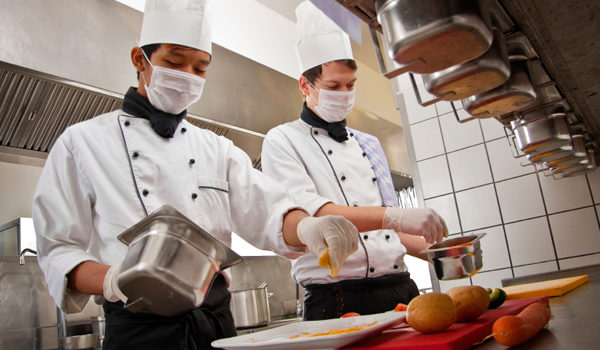 Professional Chef teaching young culinary student the art of cooking.  All images shot in a hotel's commercial kitchen.